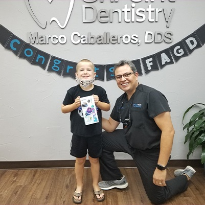 Dr. Caballeros and child at dental office