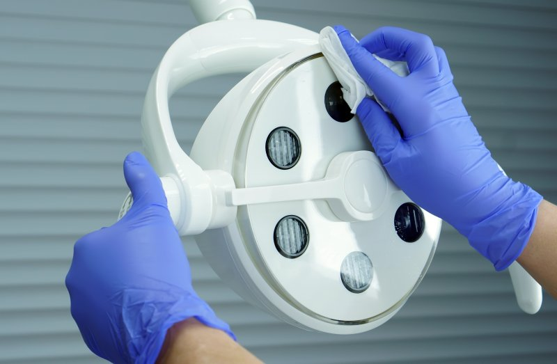 Dentist cleaning medical lamp due to COVID-19 concerns