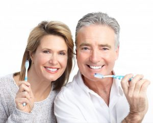 older couple brushing their teeth together